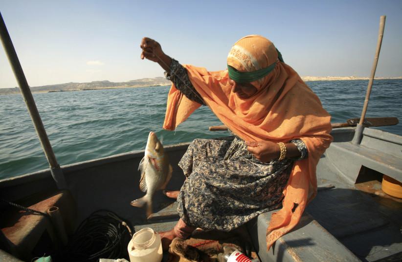 Hava Arbabi holds up fish in her boat near Hengam Island southeast of Tehran, Iran (photo credit: REUTERS/MORTEZA NIKOUBAZL)