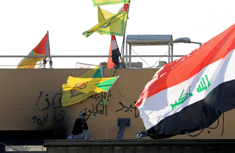 A member of Hashd al-Shaabi waves a flag of Kataib Hezbollah militia group during a protest to condemn air strikes on bases belonging to Hashd al-Shaabi (paramilitary forces), outside the U.S. Embassy in Baghdad (photo credit: REUTERS)