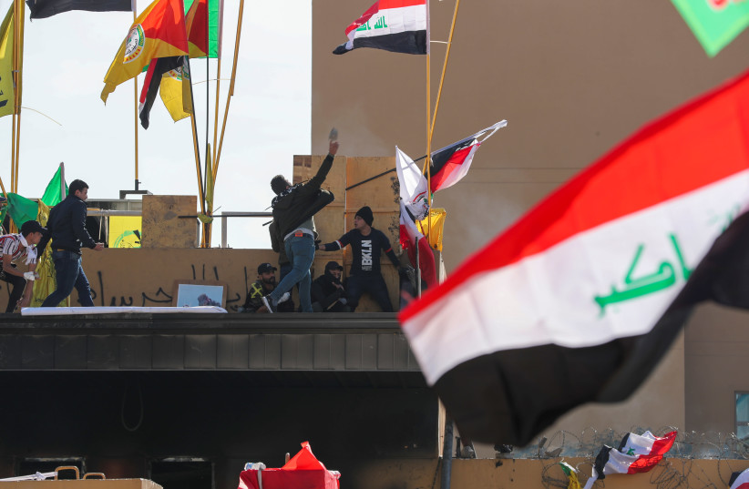 Protesters and militia fighters throw stones towards the U.S. Embassy during a protest to condemn air strikes on bases belonging to Hashd al-Shaabi (paramilitary forces), outside the U.S. Embassy in Baghdad, Iraq January 1, 2020. (photo credit: REUTERS/THAIER AL-SUDANI)