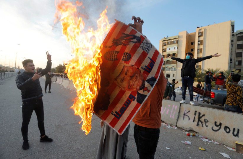 A protester holds a placard with U.S. President Donald Trump illustration burning outside the U.S. Embassy during a protest to condemn air strikes on bases belonging to Hashd al-Shaabi (paramilitary forces), in Baghdad, Iraq January 1, 2020 (photo credit: REUTERS/KHALID AL MOUSILY)