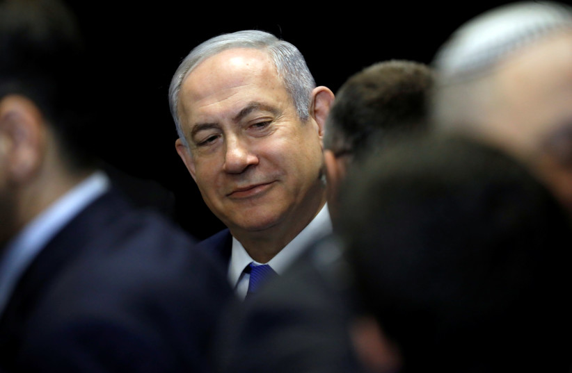 Israeli Prime Minister Benjamin Netanyahu chats with his party's members in Airport City near Tel Aviv, Israel December 27, 2019. (photo credit: AMIR COHEN/REUTERS)