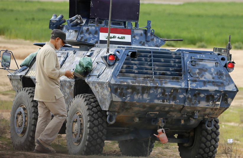 Iranian Revolutionary Guard Commander Qassem Soleimani walks near an armoured vehicle at the frontline during offensive operations against Islamic State militants in the town of Tal Ksaiba in Salahuddin province March 8, 2015. (photo credit: REUTERS/STRINGER)
