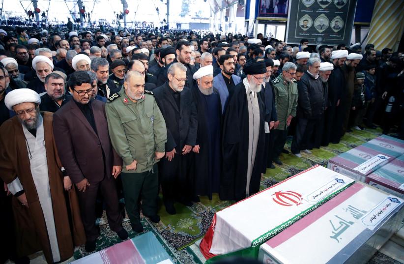 Iran's Supreme Leader Ayatollah Ali Khamenei and Iranian President Hassan Rouhani pray near the coffins of Iranian Major-General Qassem Soleimani, head of the elite Quds Force, and Iraqi militia commander Abu Mahdi al-Muhandis, who were killed in an air strike at Baghdad airport, in Tehran, Iran, Ja (photo credit: OFFICIAL PRESIDENT WEBSITE/HANDOUT VIA REUTERS)