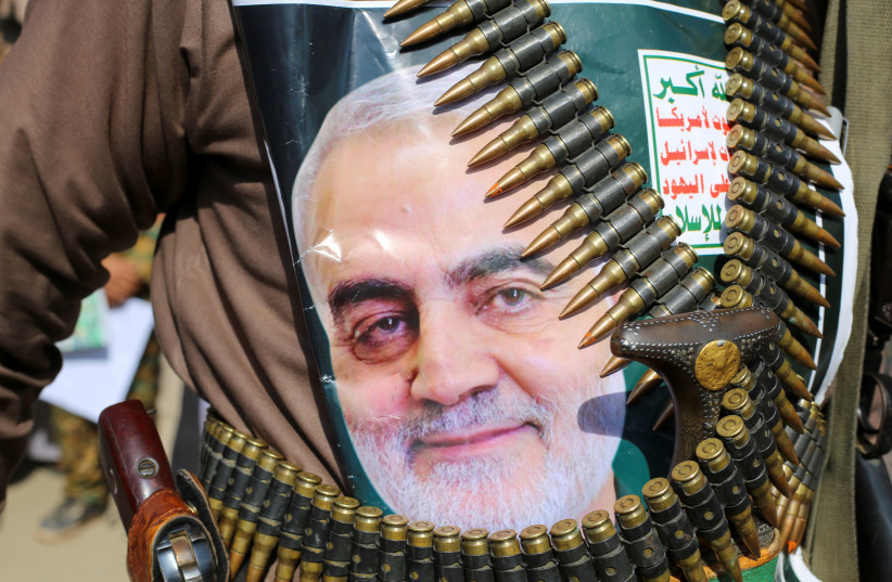 "A supporter of the Houthis has a poster attached to his waist of Iranian Major-General Qassem Soleimani, head of the elite Quds Force, who was killed in an air strike at Baghdad airport, during a rally to denounce the U.S. killing, in Saada, Yemen January 6, 2020. The writing on the poster reads: ""G (photo credit: REUTERS/NAIF RAHMA)"