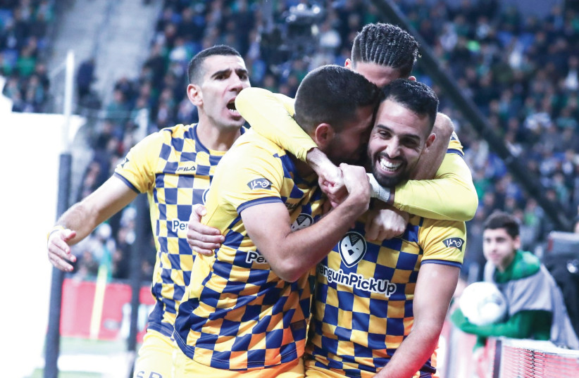 MACCABI TEL AVIV midfielder Eyal Golasa (23) celebrates with his teammates after scoring the yellow-and-blue's second goal in its 4-3 victory at Maccabi Haifa last night. (photo credit: DANNY MARON)