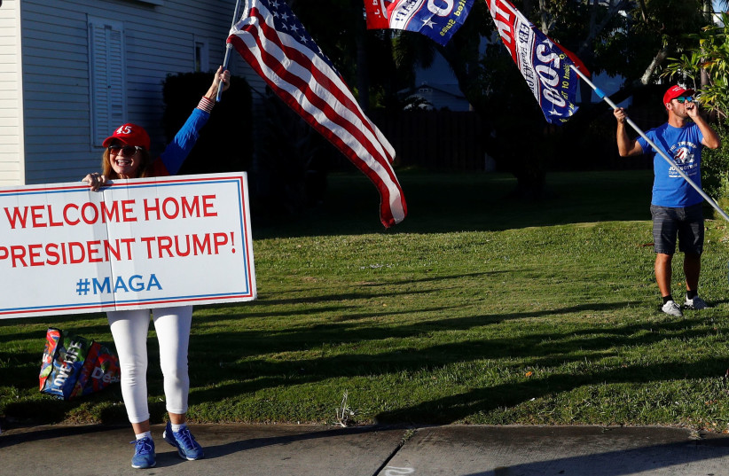PRO-TRUMP demonstrators display signs of support as the presidential motorcade drives to Palm Beach International Airport, in Florida on January 5. (photo credit: REUTERS//TOM BRENNER)