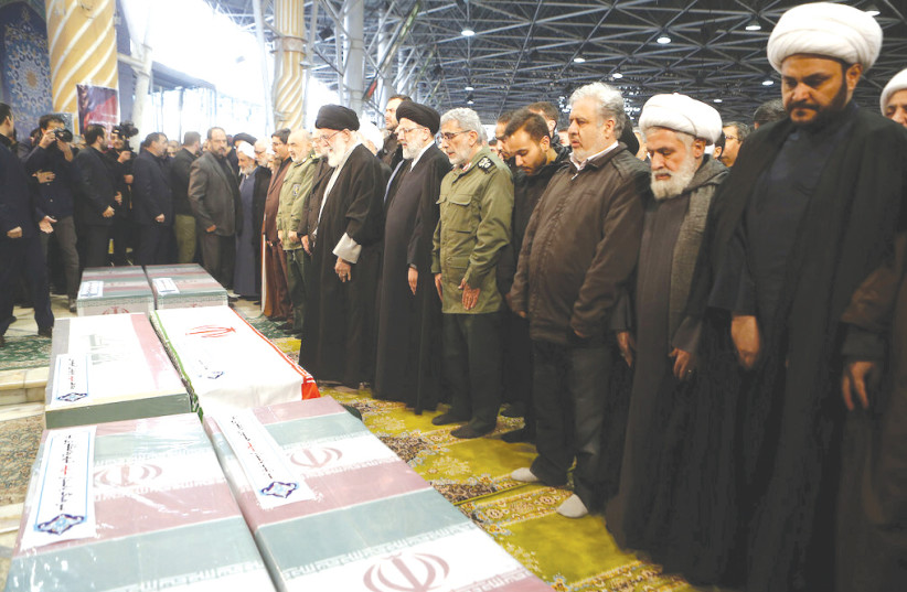 Iran's Supreme leader Ayatollah Ali Khamenei prays near the coffins of Iranian Major Qassem Soleimani and Iraqi militia commandr Abu Mahdi al-Muhandis who were killed in last wee;s US air strike at Baghdad airport.  (photo credit: REUTERS)