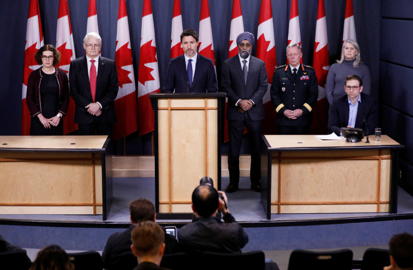 Canada's Prime Minister Justin Trudeau (C), with Deputy Minister of Foreign Affairs Marta Morgan (L), Minister of Transport Marc Garneau, Minister of National Defence Harjit Sajjan, Chief of the Defence Staff General Jonathan Vance, and Deputy Minister of National Defence Jody Thomas (R), attend a n (photo credit: REUTERS//BLAIR GABLE)