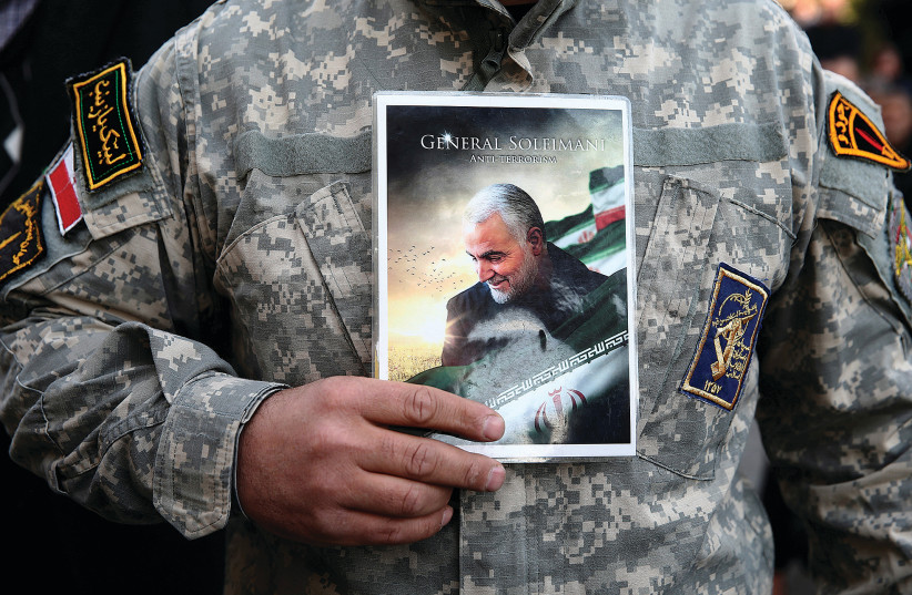 A man in uniform holds a picture of Qasem Soleimani during a protest in Tehran following his targeted assassination.  (photo credit: NAZANIN TABATABAEE/WANA VIA REUTERS)