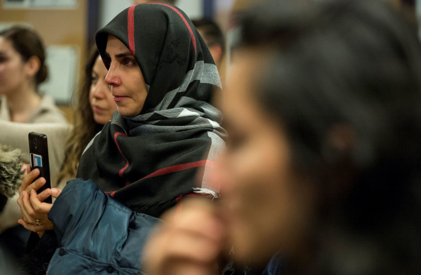 Najmeh Seilfollahpour, left, attends a vigil in memory of Iranian student Amir Moradi, who was killed in the crash of a Ukrainian passenger plane near Tehran, at Queens University in Kingston, Ontario, Canada January 10, 2020 (photo credit: REUTERS/ALEX FILIPE)