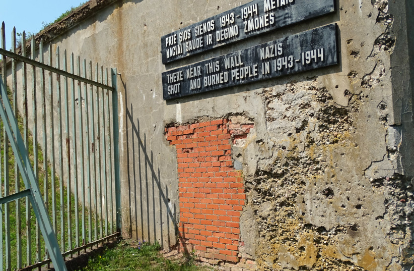 Sign with Battle-Scarred Wall - Ninth Fort - Nazi Genocide Site - Kaunas - Lithuania (photo credit: ADAM JONES/WIKIMEDIA COMMONS)