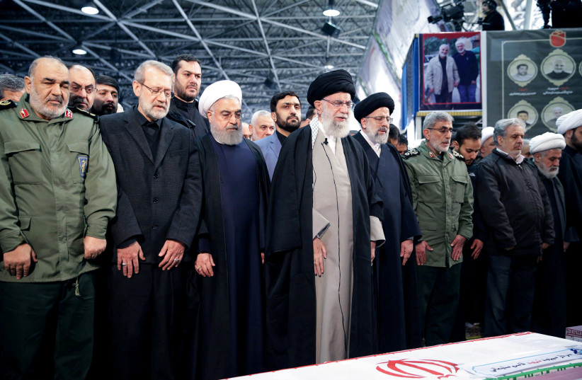 FILE PHOTO: Iran's Supreme Leader Ayatollah Ali Khamenei and Iranian President Hassan Rouhani pray near the coffin of Iranian Major-General Qassem Soleimani, head of the elite Quds Force, who was killed in an air strike at Baghdad airport, in Tehran, Iran, January 6, 2020. Official President's websi (photo credit: REUTERS)