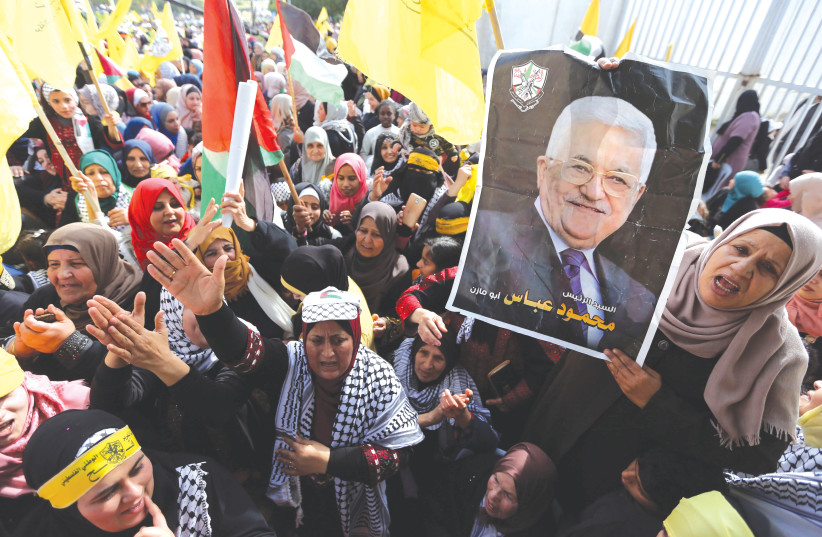 A WOMAN holds a picture of PA President Mahmoud Abbas during a rally earlier this month in Gaza City marking the 55th anniversary of Fatah's founding.  (photo credit: IBRAHEEM ABU MUSTAFA / REUTERS)
