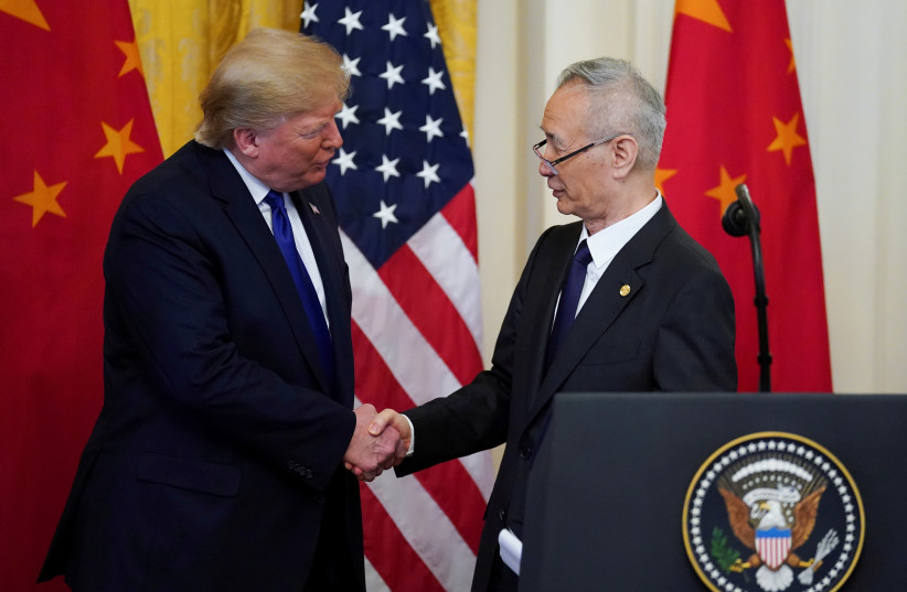 "U.S. President Donald Trump shakes hands with Chinese Vice Premier Liu He during a signing ceremony for ""phase one"" of the U.S.-China trade agreement in the East Room of the White House in Washington, U.S., January 15, 2020 (photo credit: KEVIN LAMARQUE/REUTERS)"