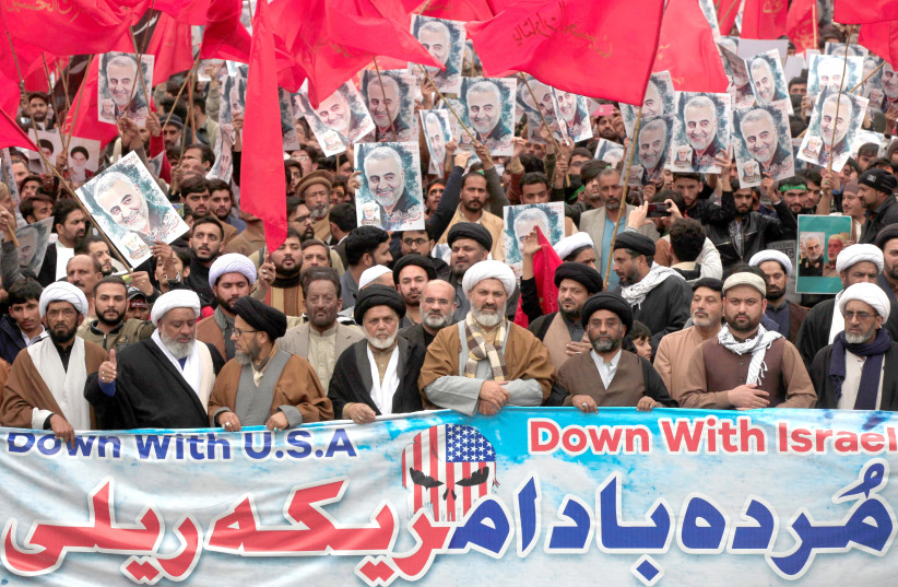 PAKISTANI SHI'ITE Muslims walk with a banner and signs during a protest against US and Israel over the death of Iranian Maj.-Gen. Qasem Soleimani, in Lahore, Pakistan, on January 12. (photo credit: REUTERS)