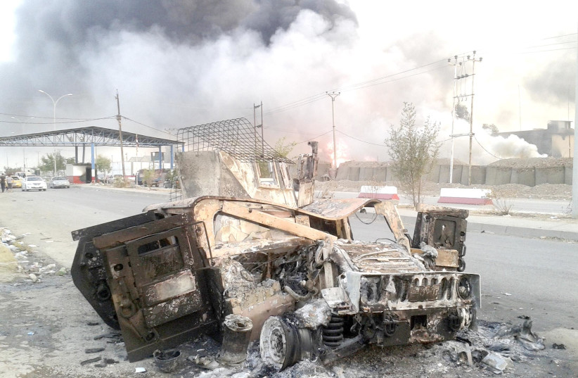 A BURNED vehicle is seen during clashes between Iraqi security forces and ISIS in Mosul in 2014.  (photo credit: REUTERS)
