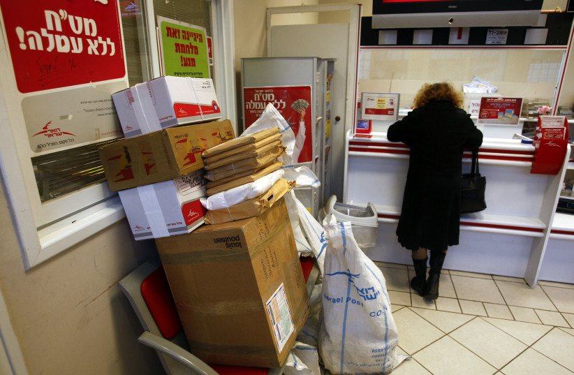A woman stands at the counter inside a Israel Post office in Jerusalem (photo credit: REUTERS/Ronen Zvulun)