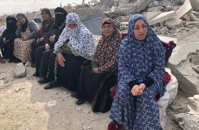 Palestinians in the Ar Rifa'iyya village sit by the rubble fo the Rib'i family home, demolished Thursday by Israeli security forces in the South Hebron Hills. (photo credit: TOVAH LAZAROFF)