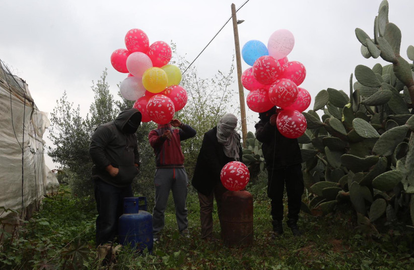Masked Palestinians release incendiary balloons near Khan Yunis in the Gaza Strip   (photo credit: MAJDI FATHI/TPS)
