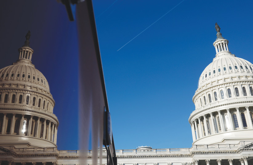 A PLANE FLIES across the sky beside the US Capitol dome in Washington last week.  (photo credit: TOM BRENNER/REUTERS)