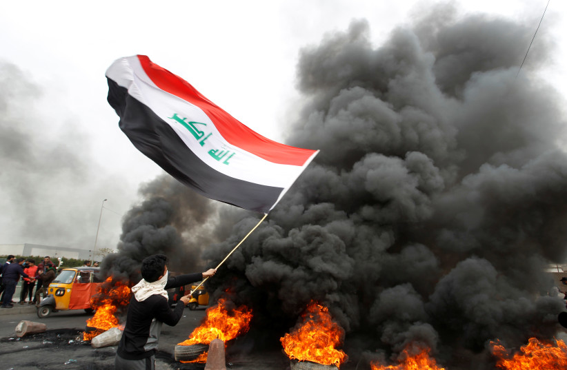 A demonstrator carries an Iraqi flag as he walks near burning tires blocking a road during ongoing anti-government protests, in Baghdad, Iraq January 19, 2020. (photo credit: KHALID AL MOUSILY / REUTERS)