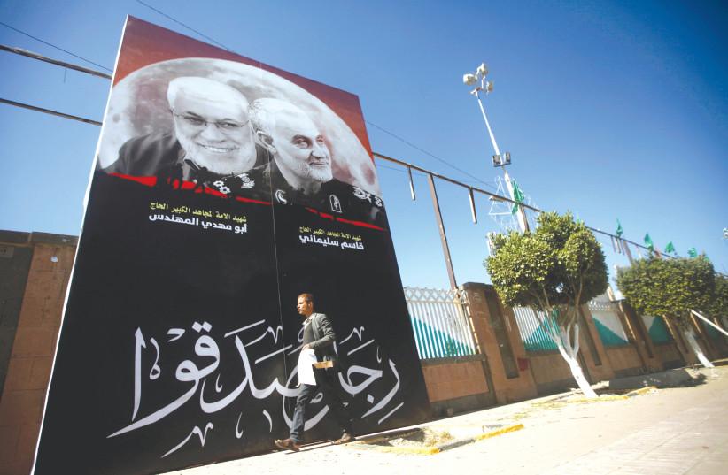 A MAN passes next to a billboard with posters of Iranian Major-General Qasem Soleimani, head of the elite Quds Force, and Iraqi militia commander Abu Mahdi al-Muhandis. (photo credit: REUTERS)