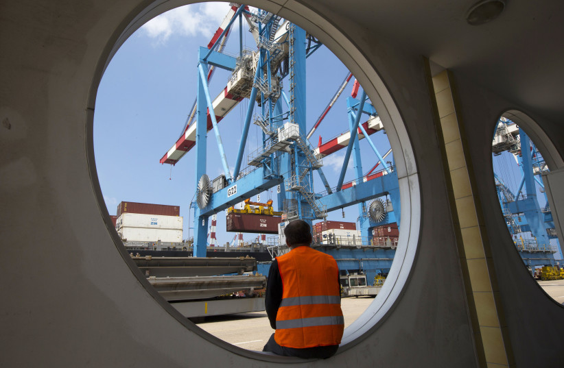 A worker sits as a crane unloads containers from a ship at the port of Haifa (photo credit: REUTERS)