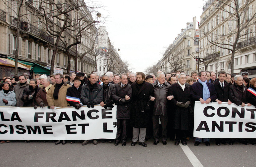 Politicians and religious leaders hold a banner reading 'France against racism and antisemitism' as they take part in a silent march through Paris in 2006 following the torture and killing of young Jewish victim Ilan Halimi. (photo credit: REUTERS/REGIS DUVIGNAU)