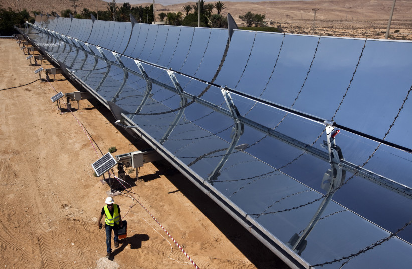 A worker walks next to parabolic mirrors at the research site of solar power company Brenmiller Energy near Dimona (photo credit: NIR ELIAS / REUTERS)
