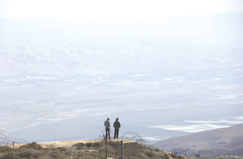 TWO ISRAELIS look over a portion of the West Bank. (photo credit: REUTERS)