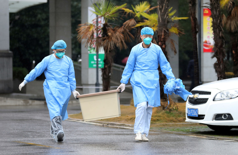FILE PHOTO - Medical staff carry a box as they walk at the Jinyintan hospital, where the patients with pneumonia caused by the new strain of coronavirus are being treated, in Wuhan, Hubei province, China January 10, 2020. Picture taken January 10, 2020 (photo credit: REUTERS/STRINGER/FILES)