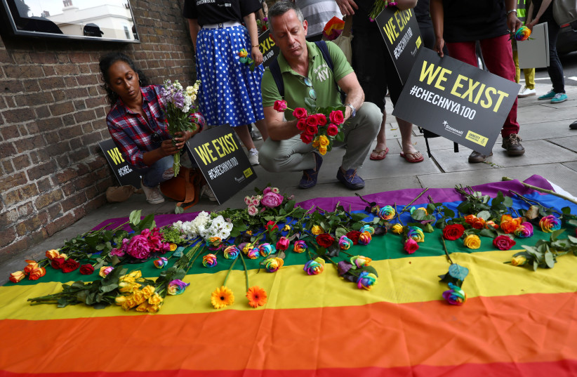 Campaigners place flowers on a multicoloured flag as they protest for LGBT rights in Chechnya outside the Russian embassy in London, Britain June 2, 2017 (photo credit: REUTERS/NEIL HALL)