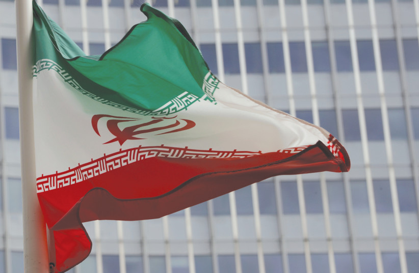 AN IRANIAN FLAG flutters in front of the International Atomic Energy Agency headquarters in Vienna last year (photo credit: REUTERS/LEONHARD FOEGER)