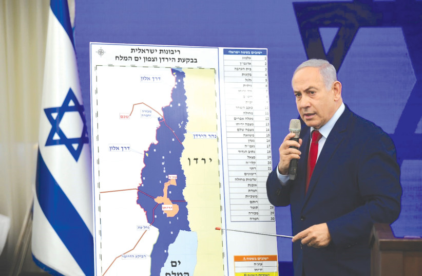 PRIME MINISTER Benjamin Netanyahu points to a map of the Jordan Valley (photo credit: YOSSI ZELIGER)