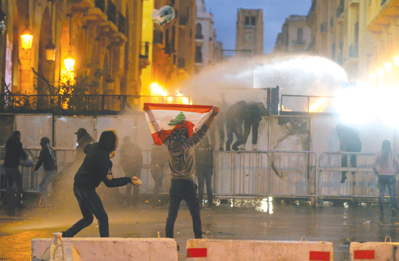 A DEMONSTRATOR IN Beirut holds up a national flag as police use water cannon during a protest against the newly formed Lebanon government earlier this week. (photo credit: REUTERS/MOHAMED AZAKIR)