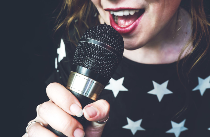 Young woman singing a song with a microphone (photo credit: INGIMAGE)