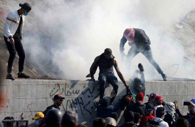 Iraqi demonstrators lift up a man who was killed during anti-government protests in Baghdad, Iraq, January 21, 2020 (photo credit: REUTERS/KHALID AL-MOUSILY/FILE PHOTO)