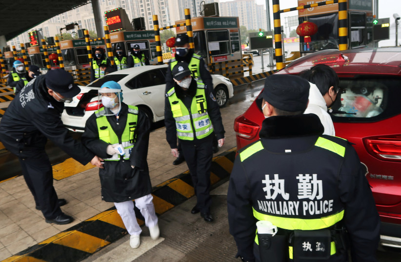 Police officers wearing masks check the boot of a car for smuggled wild animals following the outbreak of a new coronavirus, at an expressway toll station on the eve of the Chinese Lunar New Year celebrations, in Xianning (photo credit: REUTERS)