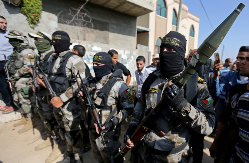 Palestinian Islamic Jihad militants take part in the funeral of their comrade in the southern Gaza Strip November 14, 2019 (photo credit: REUTERS/IBRAHEEM ABU MUSTAFA)