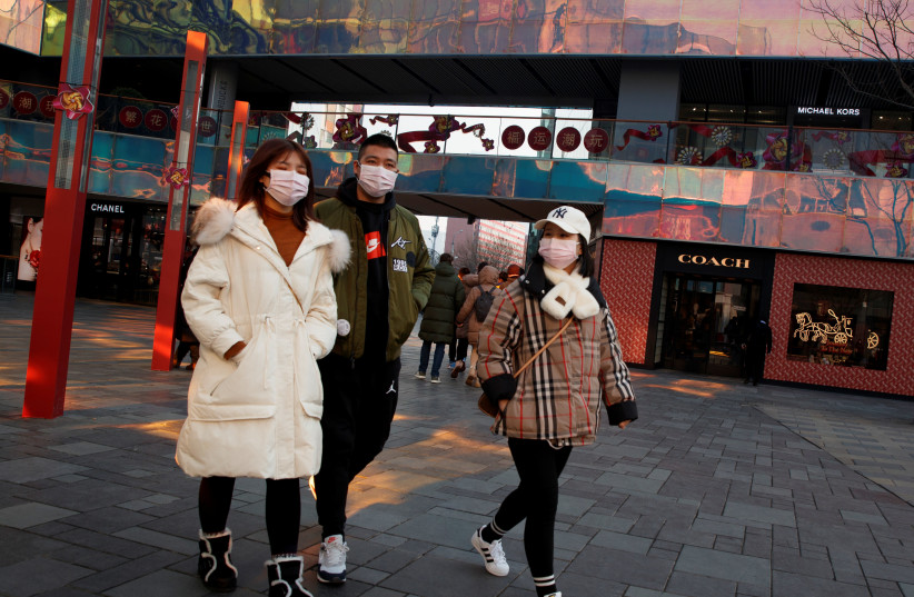 People wearing face masks walk past luxury boutiques in the Sanlitun shopping district in Beijing, China, as the country is hit by an outbreak of the new coronavirus, January 25, 2020 (photo credit: REUTERS/THOMAS PETER)