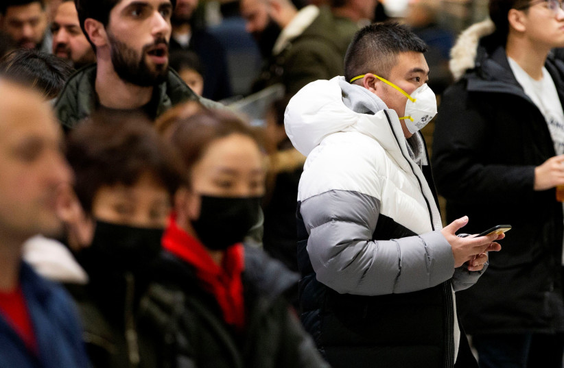 People waiting for passengers wear masks at Pearson airport arrivals, shortly after Toronto Public Health received notification of Canada's first presumptive confirmed case of coronavirus, in Toronto, Ontario, Canada January 25, 2020 (photo credit: REUTERS/CARLOS OSORIO)