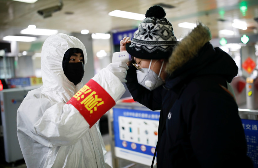 A staff member checks the temperature of a passenger entering a subway station, as the country is hit by an outbreak of the new coronavirus, in Beijing, China January 28, 2020. (photo credit: CARLOS GARCIA RAWLINS/ REUTERS)