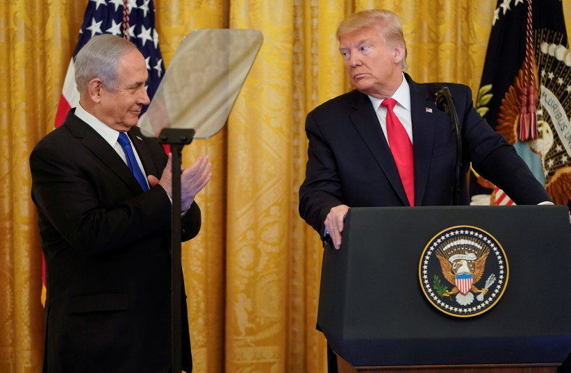 U.S. President Donald Trump looks over at Israel's Prime Minister Benjamin Netanyahu during a joint news conference to announce a new Middle East peace plan proposal in the East Room of the White House in Washington, U.S., January 28, 2020 (photo credit: REUTERS/JOSHUA ROBERTS)