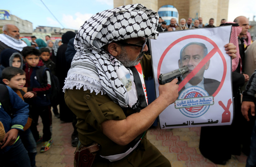 A Palestinian demonstrator points a toy gun on a poster depicting Israeli Prime Minister Benjamin Netanyahu during a protest against the U.S. Middle East peace plan, in Rafah in the southern Gaza Strip January 28, 2020 (photo credit: REUTERS/IBRAHEEM ABU MUSTAFA)