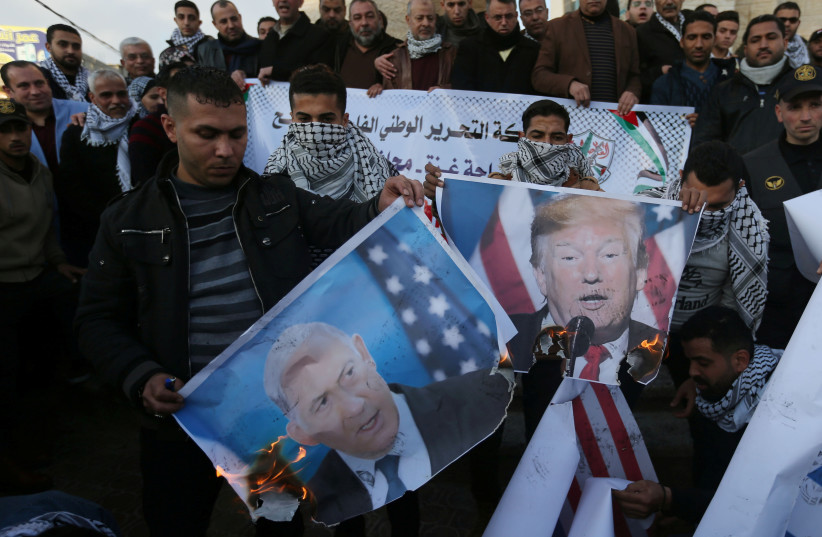 Palestinian demonstrators burn pictures depicting U.S. President Donald Trump and Israeli Prime Minister Benjamin Netanyahu, and representations of U.S and Israeli flags during a protest against the U.S. President Donald Trump's Middle East peace plan, in the southern Gaza Strip January 29, 2020.  (photo credit: IBRAHEEM ABU MUSTAFA / REUTERS)