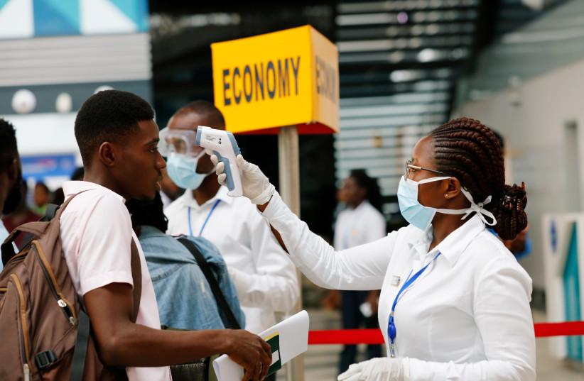 A health worker checks the temperature of a traveller as part of the coronavirus screening procedure at the Kotoka International Airport in Accra, Ghana January 30, 2020.  (photo credit: REUTERS/FRANCIS KOKOROKO)