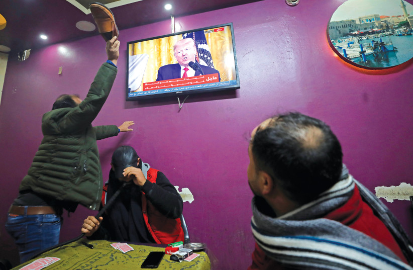 A PALESTINIAN man in a coffee shop in Hebron uses his shoe to hit a television screen broadcasting the announcement of the peace plan by US President Donald Trump on Tuesday (photo credit: REUTERS/MUSSA QAWASMA)
