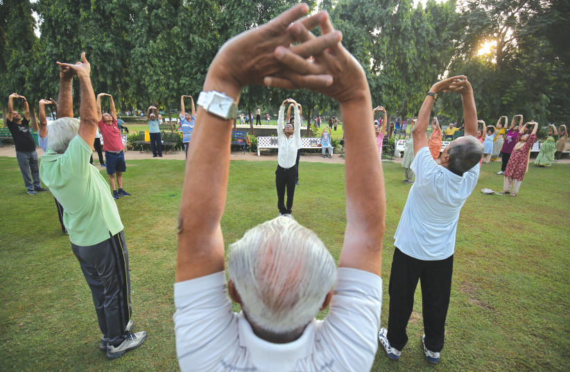 Senior citizens participate in laughter yoga in a park in India. (photo credit: AMIT DAVE)