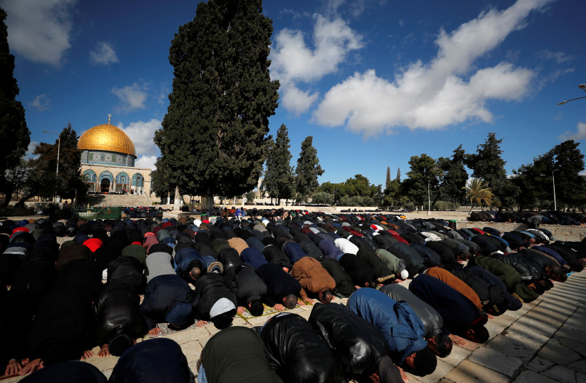 Palestinian men prays near the Dome of the Rock on the compound known to Muslims as the Noble Sanctuary and to Jews as Temple Mount in Jerusalem's Old City January 31, 2020 (photo credit: REUTERS/AMMAR AWAD)