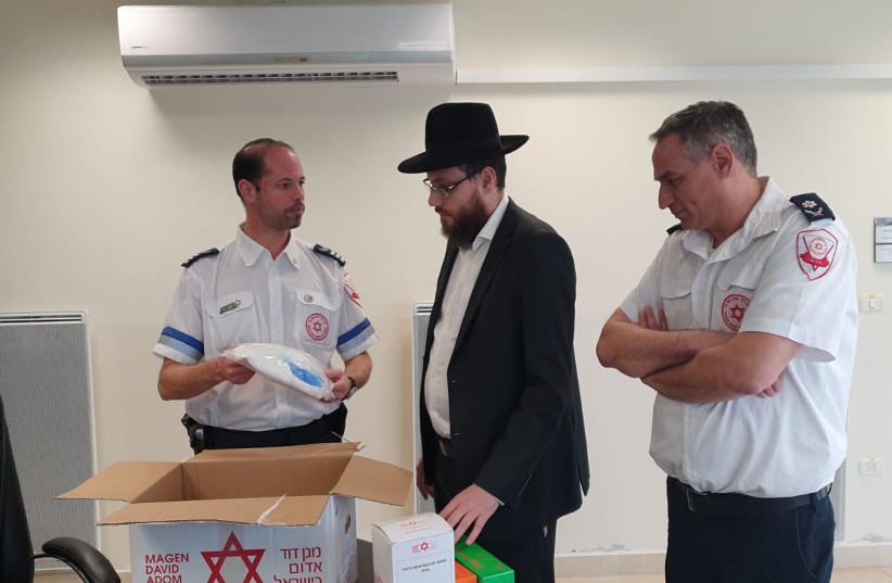 El rabino Eliyahu Rosenberg de Chabad de Guangzhou, China, examina los suministros de MDA que se enviarán a 14 casas de Chabad en toda China en un intento por prevenir la propagación del coronavirus (crédito de la foto: MAGEN DAVID ADOM)